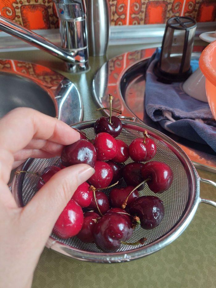 Ein Hand ist zu sehen, die Kirschen aus einem Behälter nimmt.