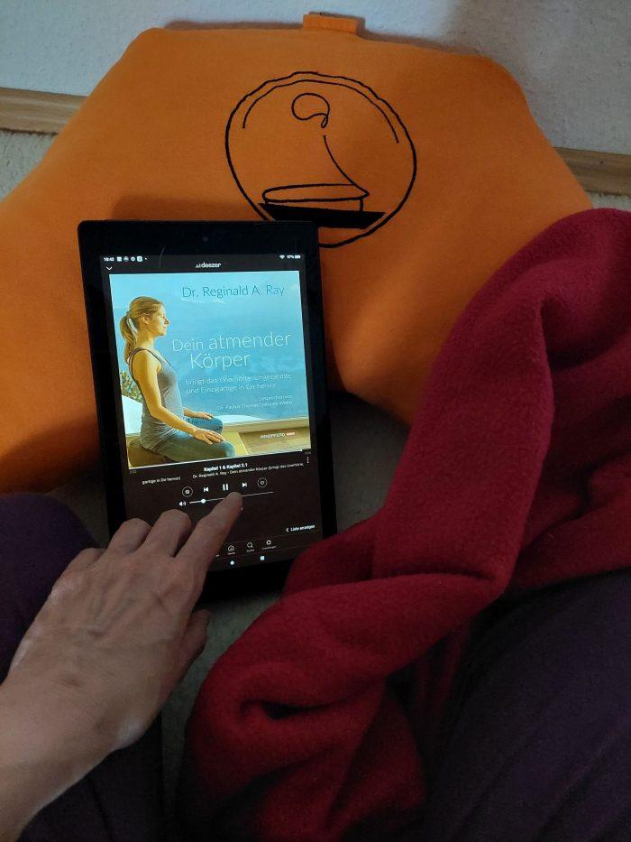 Ein IPad liegt auf einem Mediationskissen. Eine Hand bedient den Bildschirm.