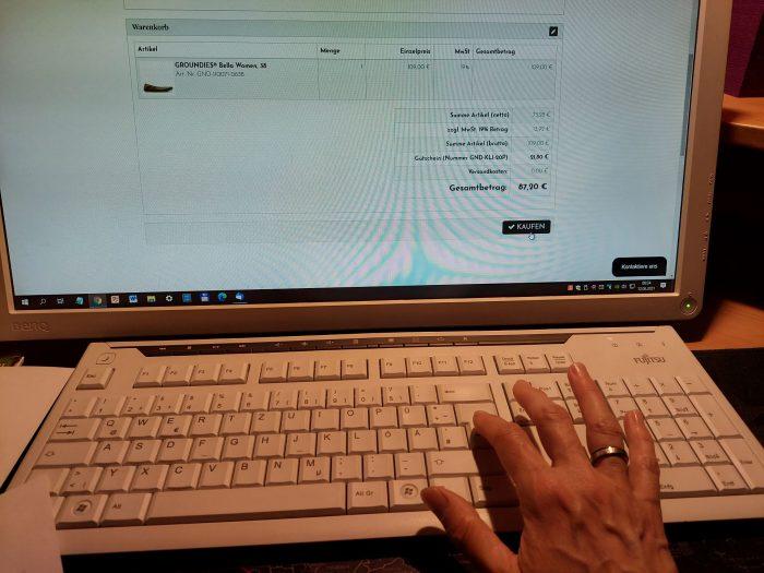 Ein Laptop ist zu sehen und eine Hand, die eine Eingabe macht.